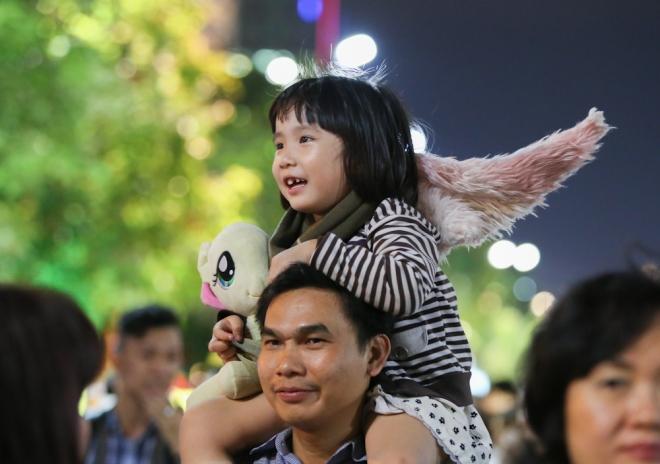 Bé Lê Thanh My (4 tuổi) thích thú khi được cha cõng trên vai dạo đường hoa.