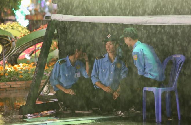 Lực lượng bảo vệ đường hoa trú mưa dưới tấm bạt.