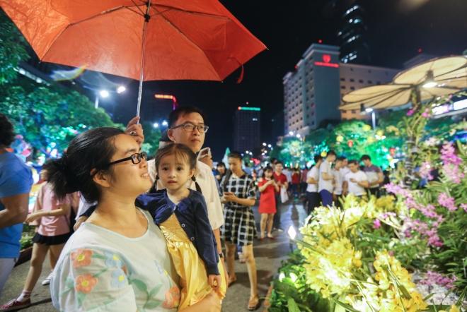Gia đình anh Huỳnh Phương chăm chú ngắm hoa duới cơn mưa lất phất.