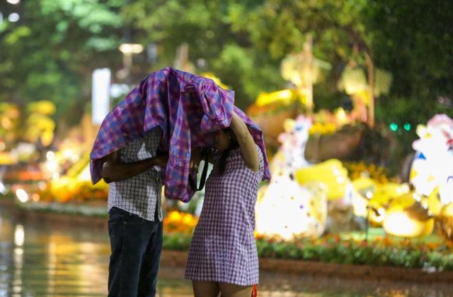 Cặp đôi trùm áo mưa để dễ coi hình ảnh đường hoa vừa chụp. Sau khoảng nửa tiếng, cơn mưa chấm dứt.